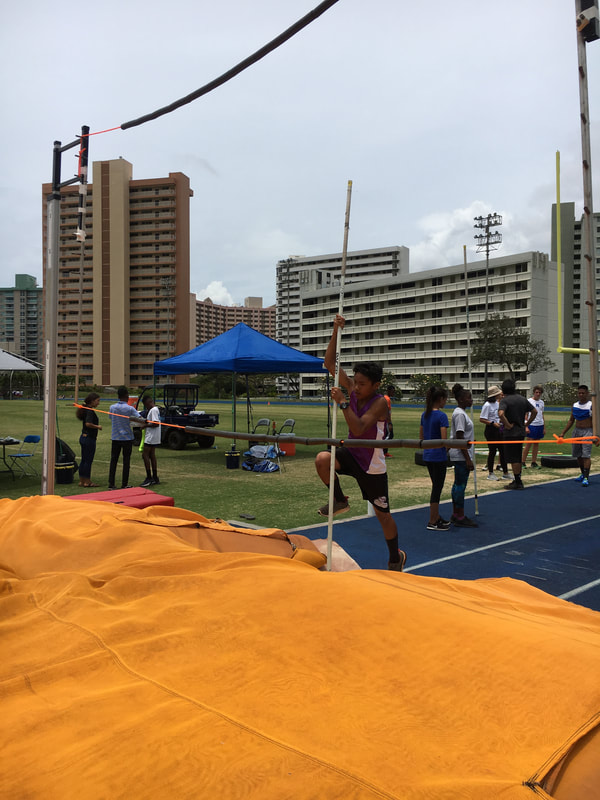 Student attempting to clear the bar in the pole vault.