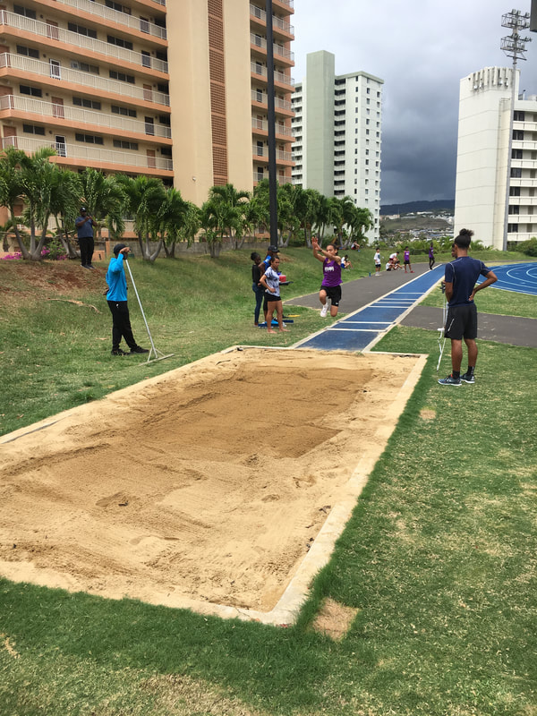 Student in mid-jump for long jump event.